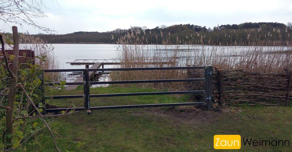 Metalltor mit Durchgangstür zum See